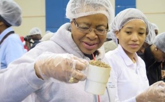 Graca Machel, Nelson Mandela's widow helping the STOP HUNGER NOW project pack 1 million meals. Photo: Louise McAuliffe/EWN
